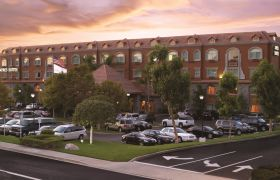 Front exterior of Ayres Suites Yorba Linda with cars in front